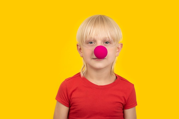 Retrato de menino loiro com nariz de palhaço em camisa vermelha