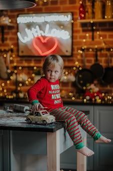 Retrato de menino loiro de pijama de natal vermelho e verde, sentado em uma mesa de cozinha