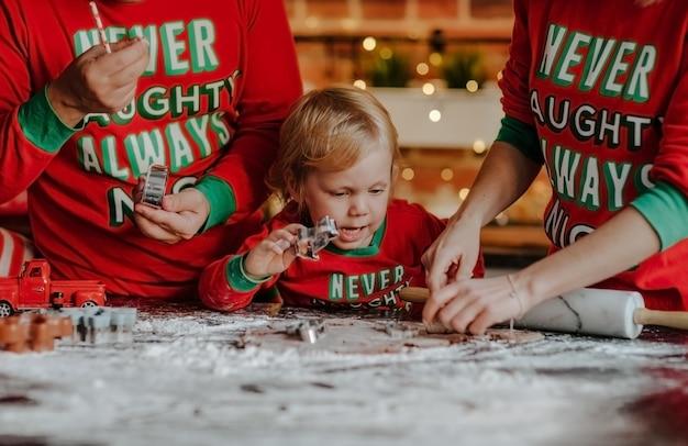 Retrato de menino loiro de pijama vermelho de natal fazendo biscoitos com a mãe e o pai