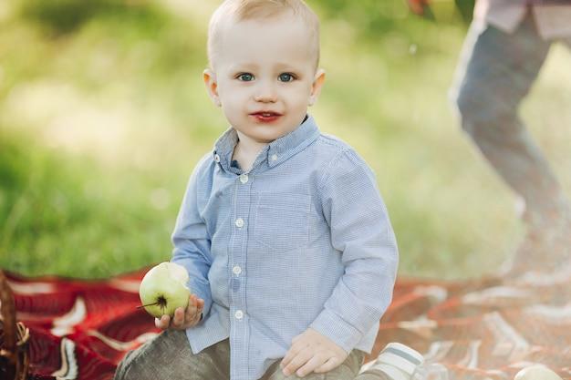 Retrato de menino loiro elegante entre grama e segurando a maçã