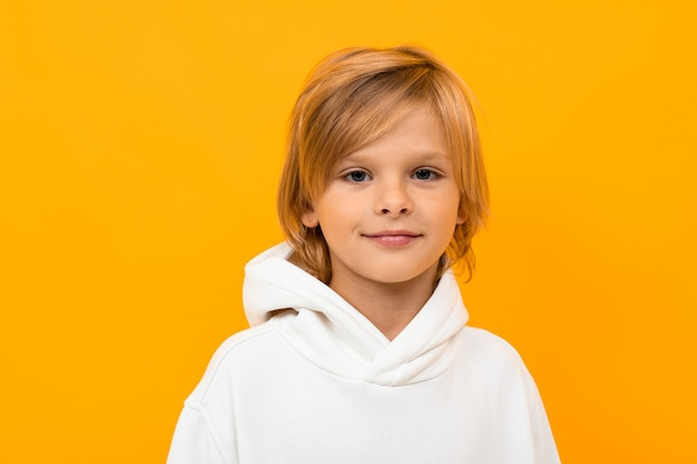 Retrato de menino loiro fazendo careta em close-up amarelo studio
