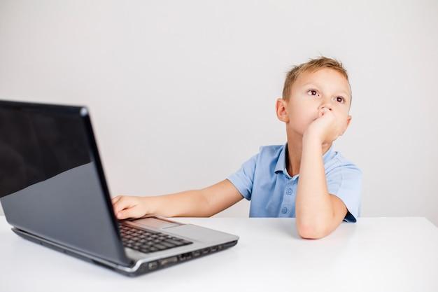Retrato de menino loiro sentado na mesa e olhando pensativamente enquanto estiver usando o laptop