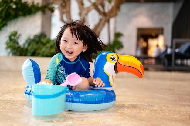 Retrato de menino na piscina no anel de flutuação de calau inflável, aprendendo a nadar