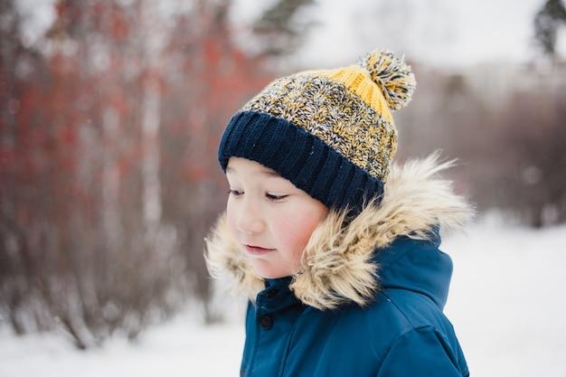 Retrato de menino no inverno, em roupas de inverno, cachecol de malha, jaqueta
