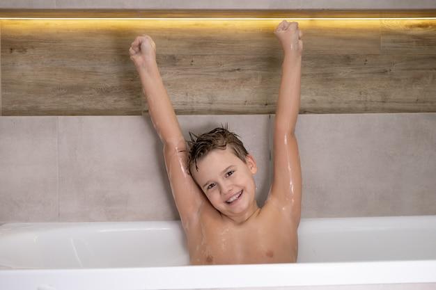 Retrato de menino nu molhado feliz no banheiro criança sorridente tomando banho em casa