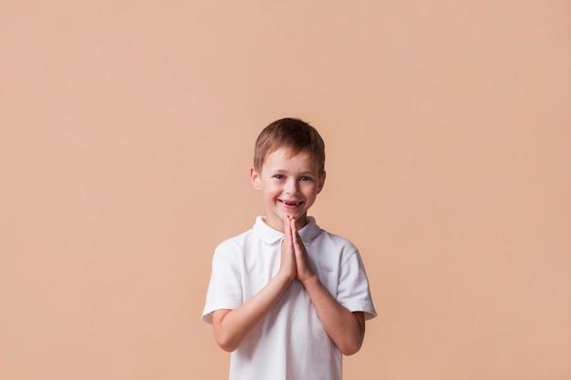 Retrato, de, menino, orando, com, um, sorrizo, ligado, seu, rosto, sobre, bege, fundo