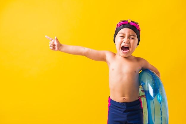 Retrato de menino pequeno asiático com óculos de proteção e maiô segurando um anel inflável azul. criança se divertindo, apontando o dedo para o lado