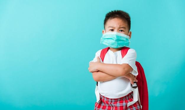 Retrato de menino pequeno asiático no jardim de infância usa máscara protetora e bolsa escolar com o braço cruzado antes de ir para a escola