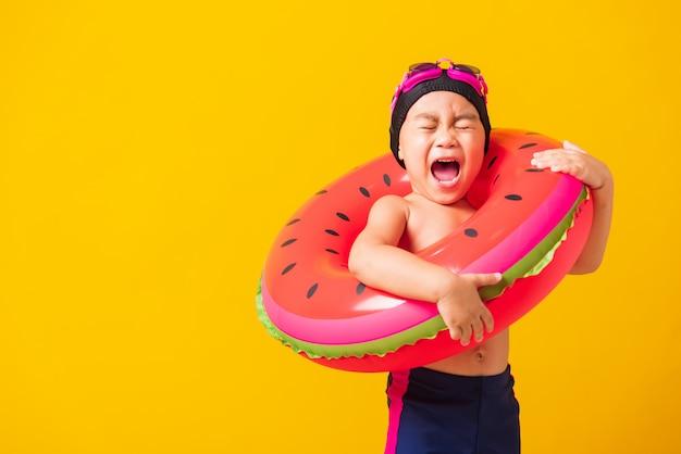 Retrato de menino pequeno asiático usando óculos e maiô segurando anel inflável de melancia