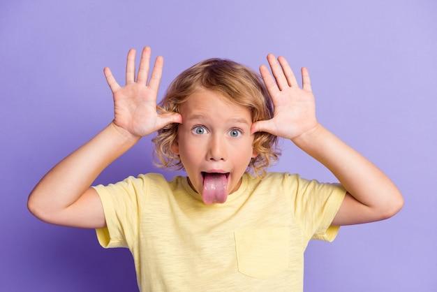 Retrato de menino pequeno fazendo cara engraçada mostrar a língua isolada sobre um fundo de cor violeta