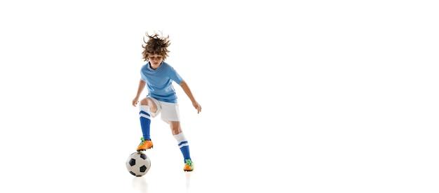 Retrato de menino pré-escolar, jogador de futebol em ação, treinamento de movimento isolado na parede branca.