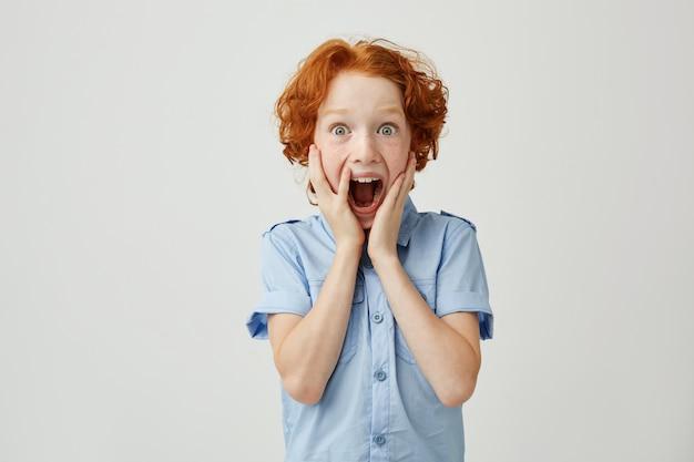 Retrato de menino ruivo com sardas, segurando as mãos nas bochechas, gritando