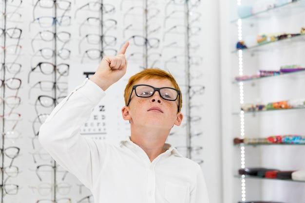 Retrato de menino sardento apontando direção ascendente na loja de óptica