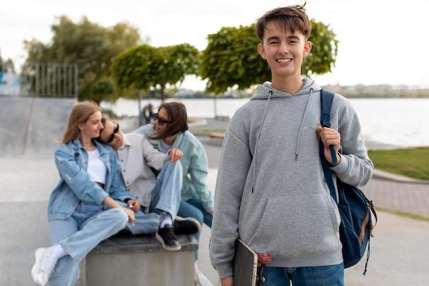 Retrato de menino segurando um skate ao lado dos amigos