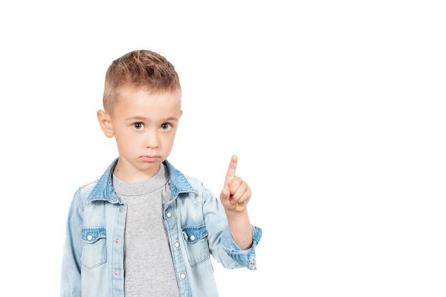 Retrato de menino sério bonito apontando para um lugar vazio no fundo, garoto surpreso, mostrando o espaço de cópia para anúncio promocional. isolado em um fundo branco