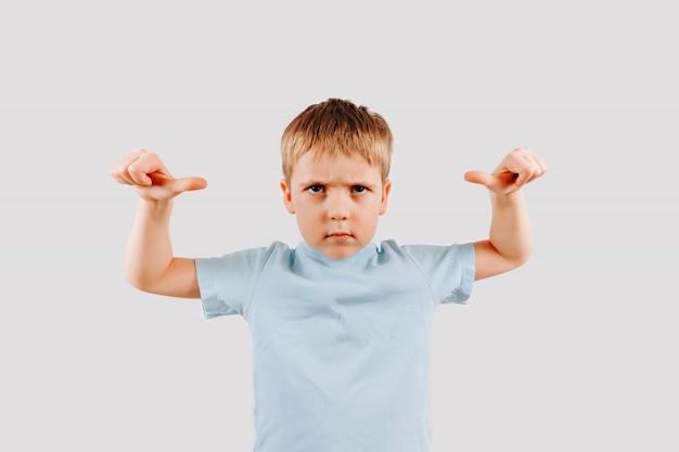 Retrato de menino sério garoto dando polegares para cima gesto com a mão