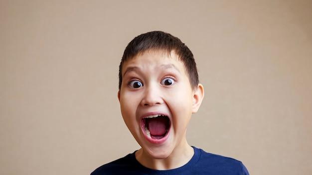 Retrato de menino sorridente, abrindo a boca em câmera lenta.