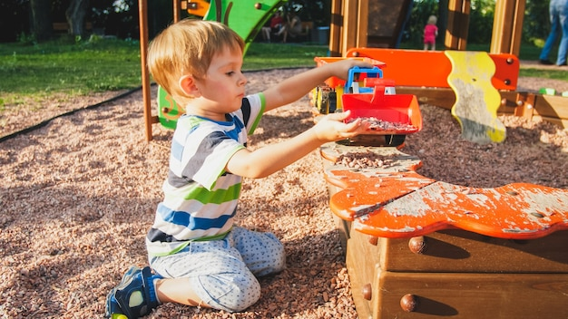 Retrato de menino sorridente alegre despejando areia no caminhão de brinquedo com reboque. crianças brincando e parquinho no parque
