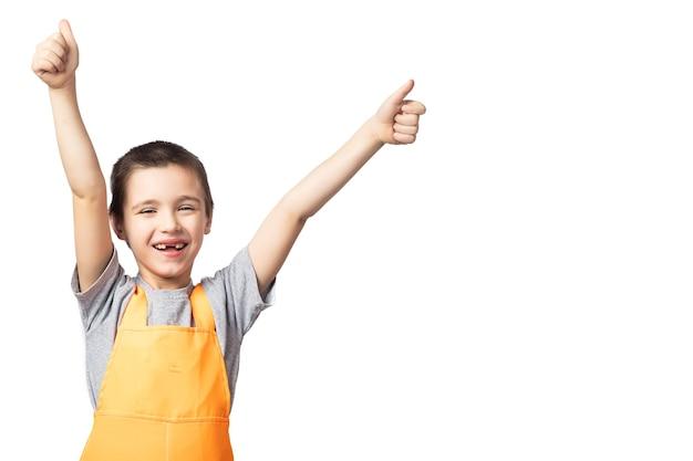 Retrato de menino sorridente, carpinteiro de macacão laranja posando, segurando, polegares para cima