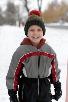 Retrato de menino sorridente com macacão e chapéu