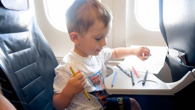 Retrato de menino sorridente da criança desenhando com lápis durante o vôo no avião.