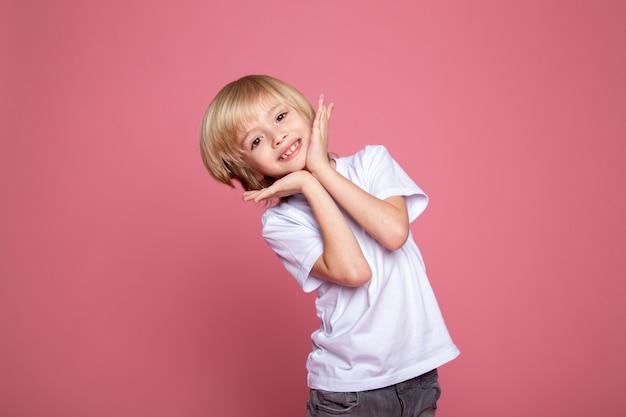 Retrato de menino sorridente de criança loira adorável fofo em camiseta branca e calça jeans cinza em backgorund rosa
