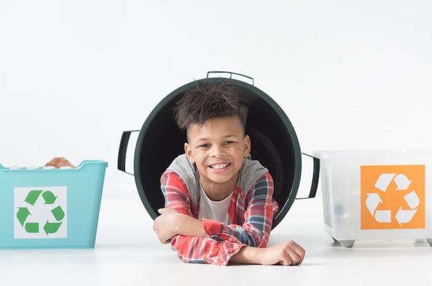 Retrato de menino sorridente posando com caixas de reciclagem