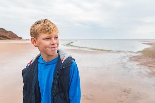 Retrato de menino sozinho na praia em dia nublado