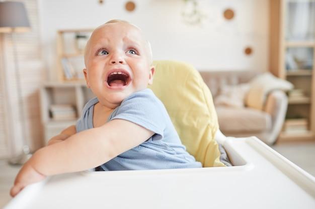 Retrato de menino travesso sentado em uma cadeira alta chorando por alguma coisa