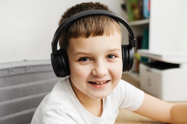 Retrato de menino usando fones de ouvido no computador