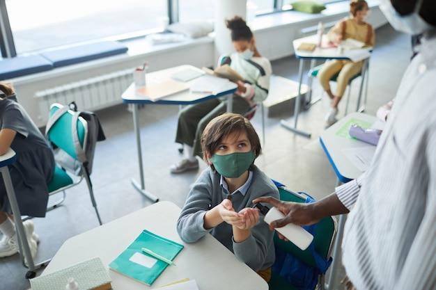 Retrato de menino usando máscara e higienizando as mãos em uma sala de aula, copie o espaço
