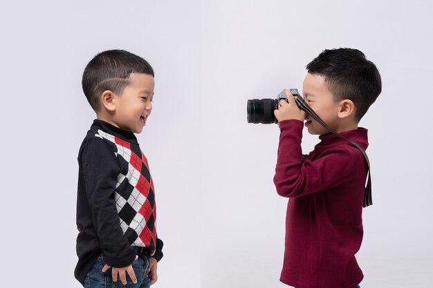 Retrato de menino vestindo uma camisola vermelha em fundo cinza, tirando foto com a câmera de filme.