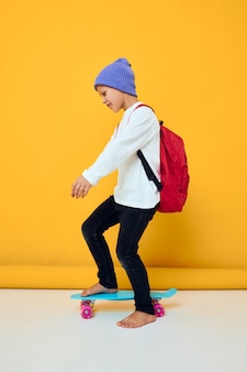 Retrato de meninos bonitos andando de skate em um conceito de estilo de vida infantil de chapéu azul