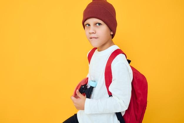 Retrato de meninos bonitos com uma mochila vermelha, um skate vermelho, um fundo de cor amarela