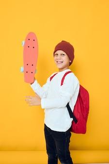 Retrato de meninos bonitos em um skate de chapéu vermelho em seu conceito de estilo de vida de infância de mãos