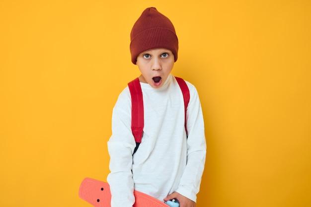 Retrato de meninos bonitos em um skate de chapéu vermelho em suas mãos com fundo de cor amarela