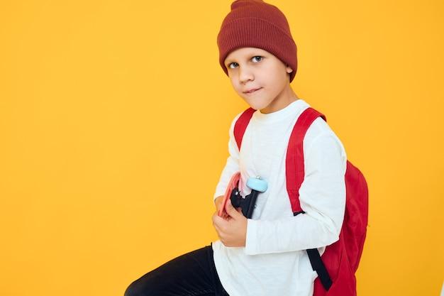 Retrato de meninos bonitos em um skate de chapéu vermelho em suas mãos isoladas de fundo