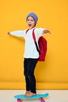 Retrato de meninos bonitos em um suéter branco skate entretenimento conceito de estilo de vida infantil