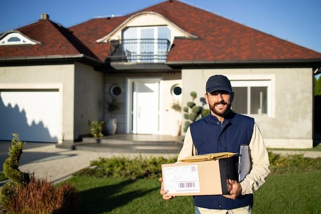 Retrato de mensageiro profissional uniformizado em pé na frente da casa entregando pacotes