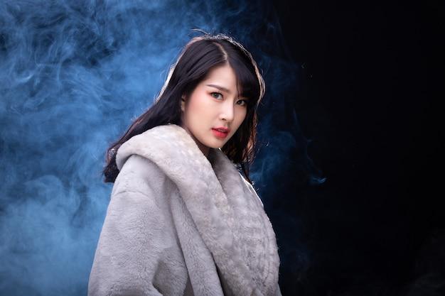 Retrato de metade do corpo de 20 mulher asiática em estilo de vestido de pele cinza de alta moda sobre fundo de névoa de fumaça com luz de fundo na parte de trás, espaço de cópia