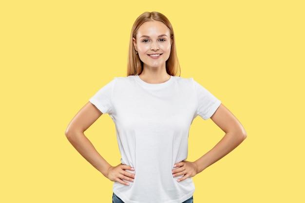 Retrato de metade do corpo de uma jovem caucasiana em estúdio amarelo