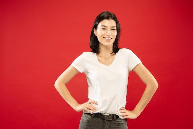 Retrato de metade do corpo de uma jovem caucasiana em estúdio vermelho