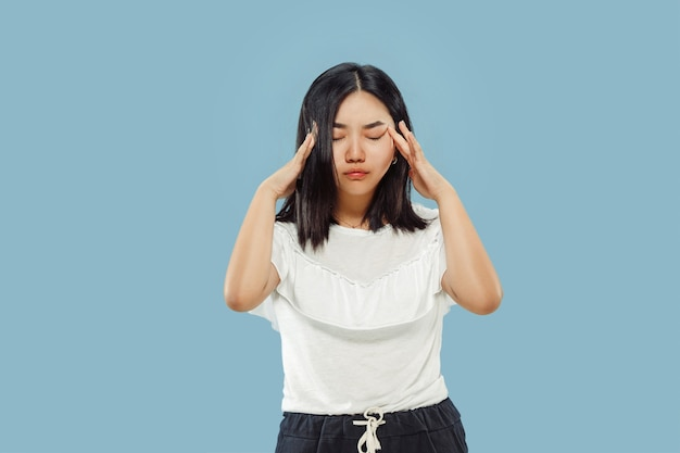 Retrato de metade do corpo de uma jovem coreana em fundo azul