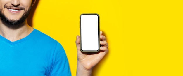 Retrato de metade do rosto de um homem segurando um smartphone com uma tela em branco na parede amarela