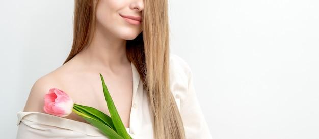 Retrato de metade do rosto de uma bela jovem caucasiana com uma tulipa rosa em fundo branco