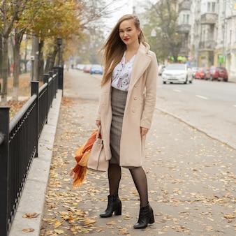 Retrato de moda ao ar livre da bela jovem elegante vestindo casaco longo bege na moda