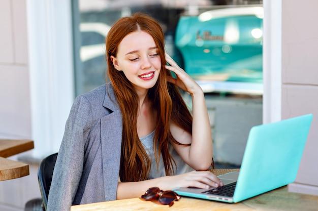 Retrato de moda ao ar livre da cidade de jovem empresária trabalhando no café no terraço em dia de sol, roupa elegante casual, detalhes de hortelã, usando seu laptop, pausa para café, conceito de negócio.