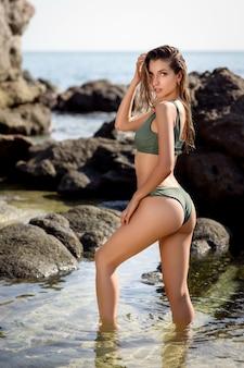Retrato de moda ao ar livre da mulher perfeita em elegantes trajes de banho, posando na praia tropical paradisíaca.