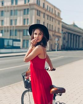 Retrato de moda ao ar livre de atraente jovem morena de chapéu em uma bicicleta.