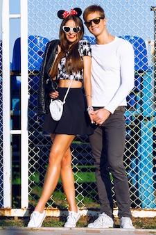 Retrato de moda ao ar livre de casal apaixonado abraços no campo de esporte, roupas da moda em preto e branco, óculos vintage, posando em um encontro romântico, dia de sol, cores brilhantes, amor, relações.
